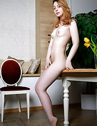 Rita Angel displays her smooth, creamy body and unshaven pussy on the chair.